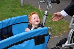 L'enfant dans le vélo de transporteur dit l'au-revoir au papa Image libre de droits