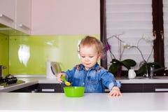 L'enfant de bébé mange de la nourriture lui-même avec la cuillère image libre de droits