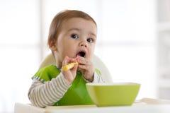 L'enfant de bébé mange de la nourriture lui-même avec la cuillère Portrait de garçon heureux d'enfant dans la chaise d'arbitre Photos stock
