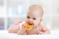 L'enfant de bébé se trouvant sur le ventre weared la couche-culotte avec le teether Photo stock