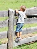 L'enfant de cheveux blonds sur une barrière en bois pense à l'avenir Photographie stock libre de droits