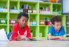 L'enfant de deux garçons fixent sur le livre de conte de plancher et de lecture dans le preschoo Image libre de droits