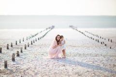 L'enfant de femme de fille de fille de mère reposent la famille d'amour de l'eau blanche de sable Photos stock