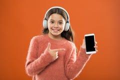 L'enfant de fille écoutent les écouteurs et le smartphone modernes de musique Détectez à l'oreille librement Obtenez l'abonnement photos libres de droits