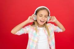 L'enfant de fille écoutent les écouteurs modernes de musique Obtenez l'abonnement de compte de musique Appréciez le concept de mu photographie stock libre de droits