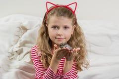 L'enfant de fille 7 années blondes avec de longs cheveux onduleux se tient dans les mains de son animal familier aimé - hamster Images libres de droits