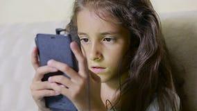 L'enfant de fille avec un téléphone portable passe en revue l'Internet écouteurs banque de vidéos