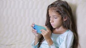 L'enfant de fille avec un téléphone portable passe en revue l'Internet banque de vidéos