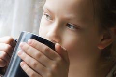 L'enfant de fille boit d'une tasse, lumière de fenêtre Photo libre de droits