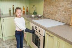 L'enfant de fille dans les gants attendant les petits pains de cuisson ou les petits gâteaux s'approchent du four Photos stock