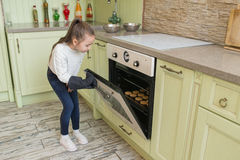 L'enfant de fille dans les gants attendant les petits pains de cuisson ou les petits gâteaux s'approchent du four Photographie stock