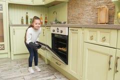 L'enfant de fille dans les gants attendant les petits pains de cuisson ou les petits gâteaux s'approchent du four Images stock
