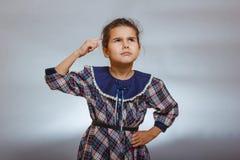 L'enfant de fille pense le doigt pour se diriger sur un gris Photos stock