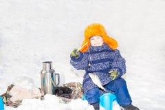 L'enfant de garçon a pêché un poisson sur une amorce l'hiver de pêche Sport d'hiver et fraise-mère Image stock