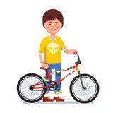 L'enfant de l'adolescence se tenant à côté de l'autocollant a bombardé le vélo de bmx Image libre de droits