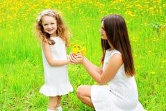 L'enfant de mère et de fille avec le pissenlit jaune fleurit en été Images stock
