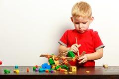 L'enfant de petit garçon jouant avec les blocs constitutifs joue l'intérieur image libre de droits