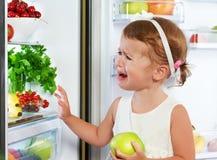 L'enfant de petite fille est pleurant et agissant au sujet du réfrigérateur avec le fruit Photo libre de droits