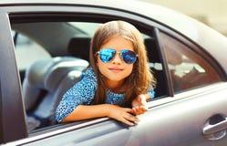 L'enfant de petite fille de portrait s'asseyant dans la voiture, passager regarde hors de la voiture photo libre de droits