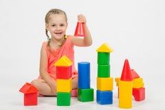 L'enfant de quatre ans a l'amusement jouant avec des blocs Images stock