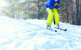 L'enfant de skieur d'hiver utilisant des vêtements de sport skie sur la neige Images libres de droits