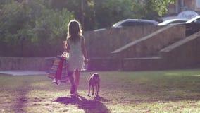 L'enfant des parents riches avec la bête à la maison et de l'achat dans des mains marche sur l'air ouvert banque de vidéos