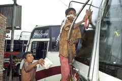 L'enfant des rues polit des autobus sur la gare routière Dhaka Photos stock