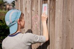 L'enfant dessinant une craie sur le mur en bois Image stock