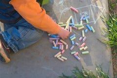 L'enfant dessine avec des crayons sur le trottoir Images libres de droits