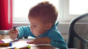 L'enfant dessine avec enthousiasme avec des crayons sur un morceau de papier Éducation préscolaire Photo libre de droits
