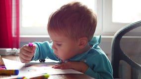 L'enfant dessine avec enthousiasme avec des crayons sur un morceau de papier Éducation préscolaire clips vidéos