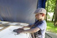 L'enfant dessine avec le sable image stock