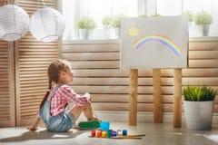 L'enfant dessine des peintures photo stock