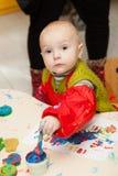 L'enfant dessine des peintures d'un doigt Photos stock