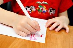 L'enfant dessine les crayons lecteurs feutres rouges Image libre de droits