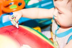 L'enfant dessine un marqueur bleu sur la boule colorée Photos stock