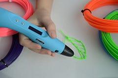 L'enfant dessine une feuille de vert du stylo 3D Image libre de droits