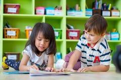 L'enfant deux fixent sur le livre de conte de plancher et de lecture dans la bibliothèque préscolaire images libres de droits