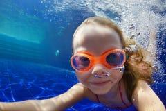 L'enfant drôle dans les lunettes plongent dans la piscine photos libres de droits