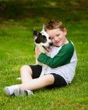 L'enfant embrasse affectueusement son chien Image libre de droits