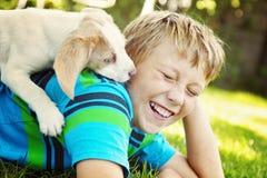 L'enfant embrasse affectueusement son chien Photographie stock