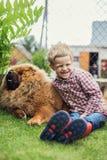 L'enfant embrasse affectueusement son chien Chow Chow Image stock