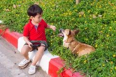 L'enfant embrasse affectueusement son chien, corgi d'un pembroke photo libre de droits