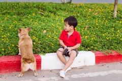 L'enfant embrasse affectueusement son chien, corgi d'un pembroke Images stock
