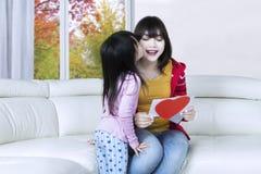 L'enfant embrassent sa maman sur le sofa Photographie stock libre de droits