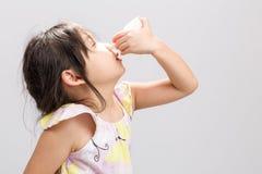L'enfant employant le fond/enfant de pulvérisation nasale employant la pulvérisation nasale/enfant à l'aide de la pulvérisation n Image libre de droits