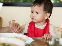 L'enfant en bas âge asiatique apprennent à manger le repas elle-même Images stock