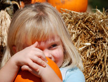 L'enfant en bas âge blond étreint le potiron Image libre de droits