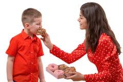 L'enfant en bas âge de bébé garçon mangent le beignet doux une femme alimente un bébé avec un beignet photographie stock libre de droits