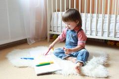 L'enfant en bas âge dessine avec des stylos de feutre à la maison Image libre de droits